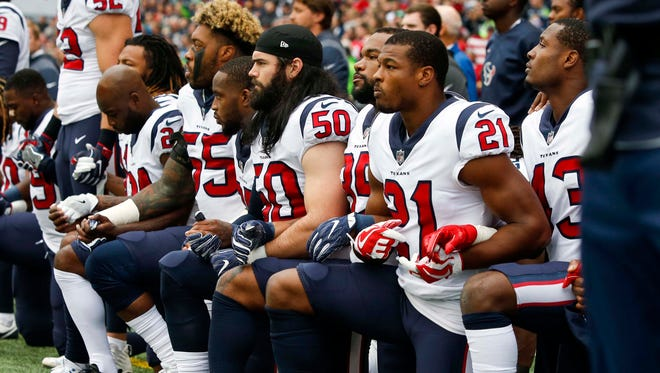 Houston Texans inside linebacker Benardrick McKinney (55), linebacker Ben Heeney (50), strong safety Marcus Gilchrist (21) and teammates kneel during the national anthem before kickoff against the Seattle Seahawks at CenturyLink Field.