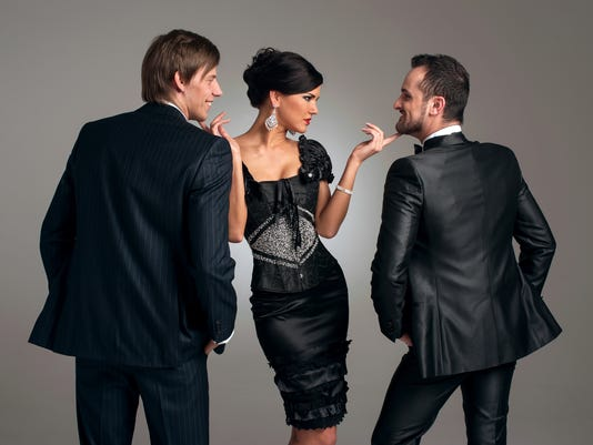 A woman in a black dress between two men in suits