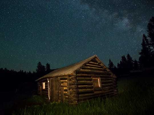 Lit up beneath the night sky, a cabin at Garnet ghost town exposes the remote nature of the 1870s Montana ghost town.