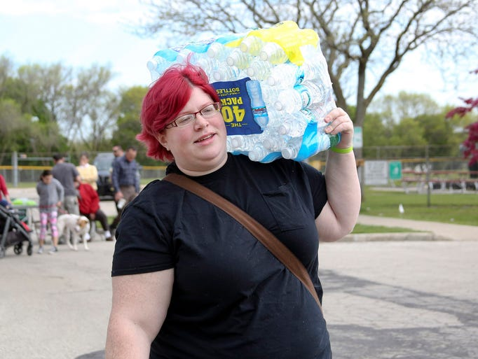 Danika Pulvermacher carries water to a table for participants