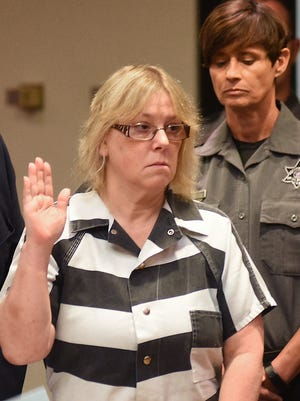 In this July 28, 2015, file photo, Joyce Mitchell raises her hand during a court appearance in Plattsburgh, N.Y. Mitchell is a former New York prison employee who helped two killers escape from a maximum-security prison in June.