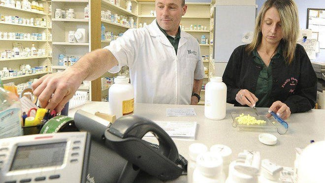 Pharmacy tech Rachael Beard works with pharmacist Tim Mitchell on Thursday at Mitchell's Drug Store in Neosho.