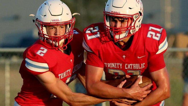 Trinity Catholic's Lucas Hammeke (2) hands the ball off to Andrew Bergmeier (21) during their game against Inman Friday night. Trinity defeated Inman 26-20.