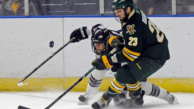 Vermont's Connor Brickley (23) and Union's Mat Brodie fight for a loose puck during the second period during a game in the men's NCAA East Regional hockey tournament Friday in Bridgeport, Conn.