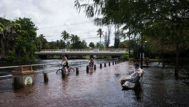 Jack Cannon, 14, left, and Salvador Figueroa, 13, both of Bonita Springs, ride their bikes on a flooded walkway as Jerry Rabin watches from a bench at Riverside Park in Bonita Springs on Monday, Aug. 28, 2017.