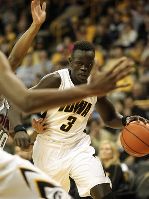 Iowa's Peter Jok drives around a Nebraska-Omaha defender during their game at Carver-Hawkeye Arena on Sunday, Nov. 10, 2013.