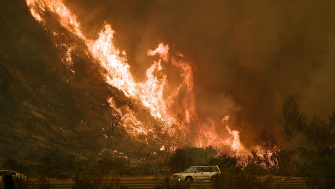Vehicles pass beside a wall of flames on the 101 highway as it reaches the coast during the Thomas wildfire near Ventura, Calif., on Dec. 6.