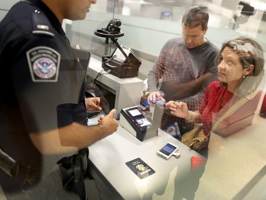 Personas que intentan a cruzar hacia Estados Unidos son interrogadas por un oficial de aduanas.