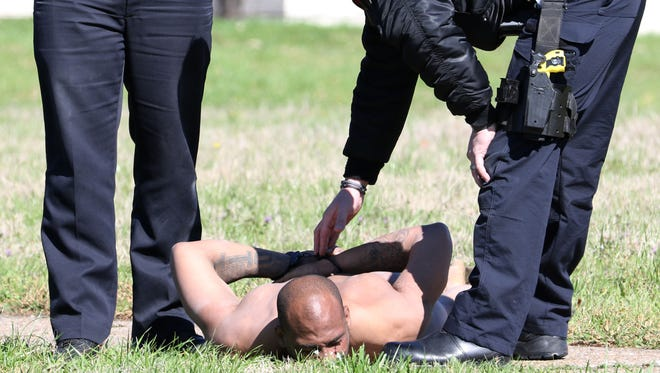 Monroe police officers subdue a man who was roaming naked in the area around Conrad Drive in Richwood on Thursday.