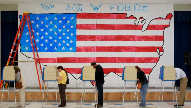 Voters cast their ballots on Election Day in front of a stage decoration for a Veterans Day event at Robious Elementary School in Midlothian, Virginia.