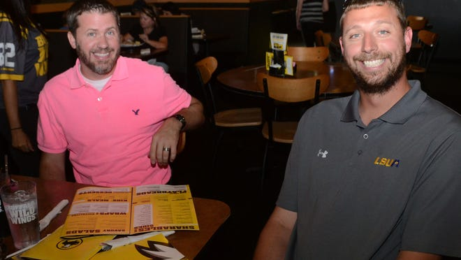 Deron Thaxton (left), vice chancellor at LSUA , and Bob Austin, LSUA women's basketball coach watch the LSUA Women's softball team take on Lindsey Wilson in the NAIA Softball World Series held in Sioux City, Iowa. They and other LSUA fans were watching the game at Buffalo Wild Wings.