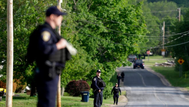 Law enforcement officers line a street near an area during a search for two escaped prisoners near Dannemora, N.Y., Thursday.