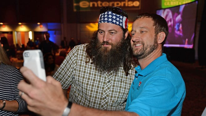 "Brian Lamb of Bossier City snaps a ""selfie"" with Willie Robertson of Duck Dynasty while attending the Duck Commander Independence Bowl Kickoff Luncheon Wednesday afternoon at the Shreveport Convention Center."