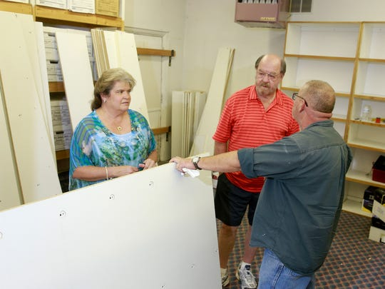 Tammy and Jerry Stansbury, owners of Front Row Seat Used Movies, talk with Art Valdez, right, while preparing for their opening on Wednesday at  the corner of West Main Street and North Allen Avenue in Farmington.
