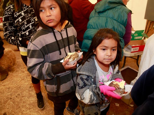 Erik Lopez, 11, left, and Aaliyah Williams, 6, right, wait in line for drinks after getting a baked potato during last year's customer appreciation day at the NAPI Region 2 Complex south of Farmington.