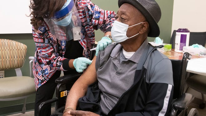 Registered Nurse Linda Hixson prepares to give Joe Knight his first dose of the COVID-19 vaccine on Tuesday, Jan. 12. Knight, a veteran of the Korean and Vietnam wars, is the first outpatient veteran to receive the new Moderna vaccine at the Joint Ambulatory Care Center in Pensacola, Florida.