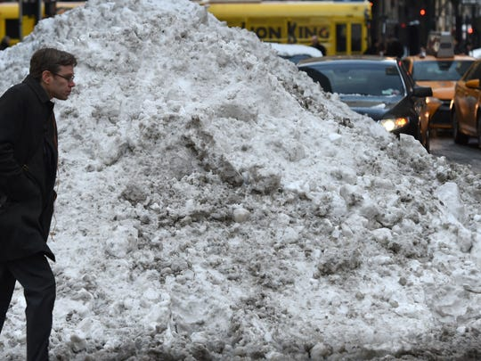 People walk past a large bank of snow on Park Avenue