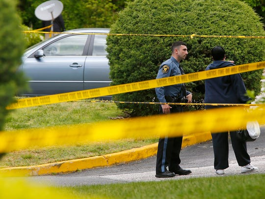A Neptune Township police officers speaks with a resident outside building 8 at the Jumping Brook West Apartment complex off Route 33 in the township Monday, May 15, 2017.   Police have confirmed that a man was struck by gunfire.