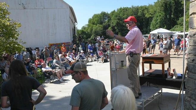 Matt Kiko looks for bids during Saturday's auction at the Kishman family farm near Minerva.