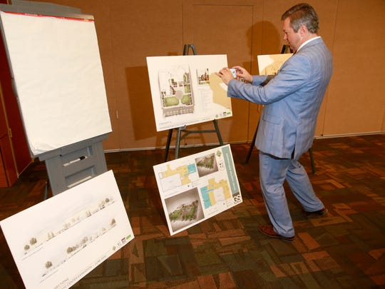 Scott Michlin, who lives near the Farmington Civic Center, takes photos on Monday of the architectural drawings for possible renovations at the Civic Center.