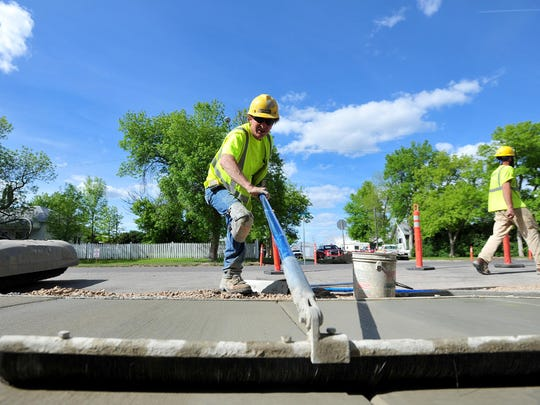 A United Materials concrete finisher brushes wet concrete on a project to add handicap ramps at sidewalk corners along 8th Street North on Tuesday afternoon.