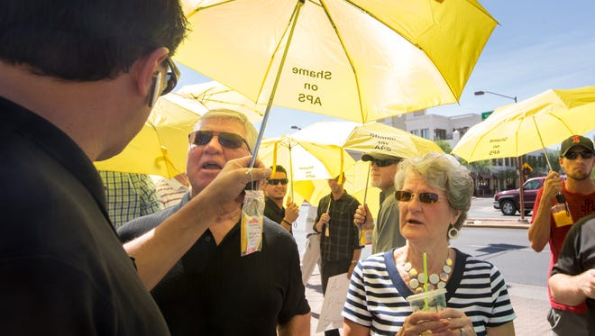 Rick Mason, with the Arizona Solar Solutions, right, chats with Paul and Sue Mark, of Peoria, before a dark money protest against Arizona Public Service over the big campaign donations on Corporation Commission and Secretary of State races, outside APS headquarters in downtown Phoenix, on Tuesday, July 29, 2014.