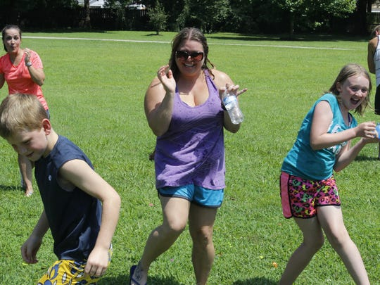 Kimberly Born and Haley Flowers duck as water balloons narrowly miss them at a water balloon fight.