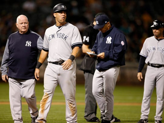 Yankees catcher Gary Sanchez (24) exits the game accompanied
