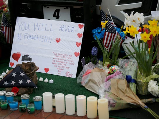 Mourners gather and leave flowers on a police cruiser