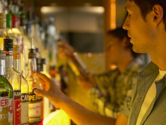 """Bartender reaching for bottle of spirits, close-up"""