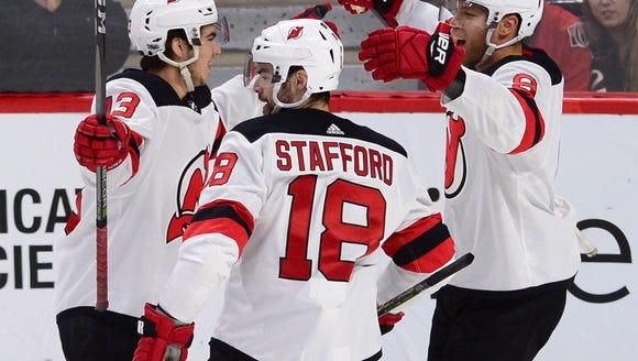 New Jersey Devils' Nico Hischier, left, celebrates