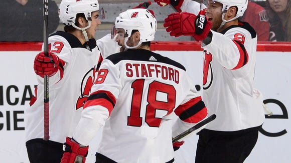 New Jersey Devils' Nico Hischier, left, celebrates his goal against the Ottawa Senators with teammates Drew Stafford (18) and Taylor Hall (9) during the first period of an NHL hockey game, Thursday, Oct. 19, 2017 in Ottawa, Ontario. (Sean Kilpatrick/The Canadian Press via AP)