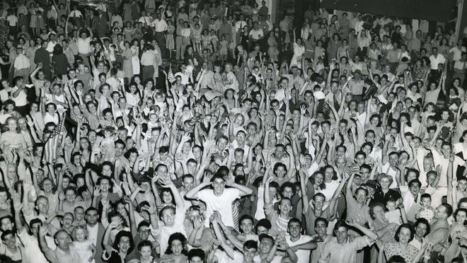 A massive crowd gathers Aug. 14, 1945, off Bowery Street as Akron residents celebrate the end of World War II on V-J Day.
