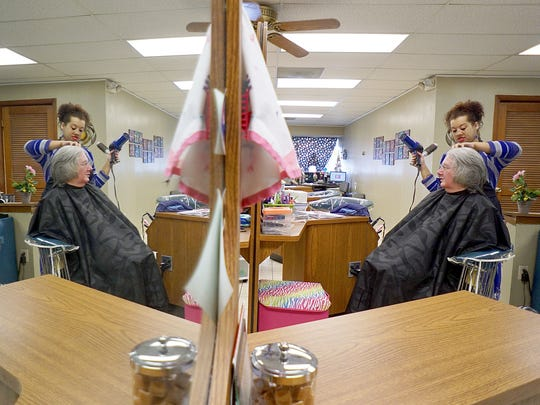 Stylist Mikayla Kahl works on the hair of Paula Harman on Tuesday morning at Downtown Hair Designers.