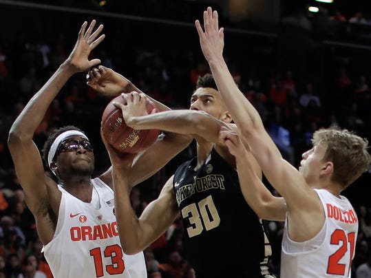 Wake Forest center Olivier Sarr (30) is double-teamed by Syracuse center Paschal Chukwu (13) and forward Marek Dolezaj (21) during the first half of an NCAA college basketball game in the Atlantic Coast Conference men's tournament Tuesday, March 6, 2018, in New York. (AP Photo/Julie Jacobson)
