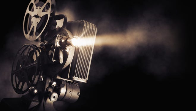 An old-school movie projector shoots light as reels of film circle above the projector.