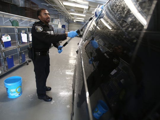 Macomb County Sheriff's Department animal control officer Val Charleston, 31 of Hazel Park washes the Ford Expedition he drives for the job inside the Macomb County Animal Shelter in Clinton Township on Friday, February 5, 2016. Usually a trustee does jobs like this but after the sheriff's department cut the program, workers at the shelter had to take on new responsibilities.