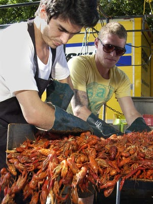 Josh Hefner, left, and Tommy Herter of Mike?s Mudbugs help serve about 125 pounds of crawfish. 5-1-11, 1c  (l-r) Josh Hefner and Tommy Herter of Mudbug Mike's help serve up about 125lbs of crawfish Friday afternoon at the 27th annual Pensacola Crawfish Festival.
