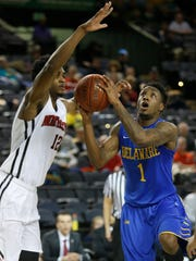 Delaware's Kory Holden drives on Northeastern's Quincy Ford in the first half of a CAA tournament quarterfinal at the Royal Farms Arena in Baltimore Saturday.