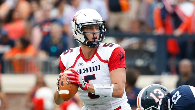 Richmond Spiders quarterback Kyle Lauletta (5) looks to pass the ball against the Virginia Cavaliers during the first half at Scott Stadium.