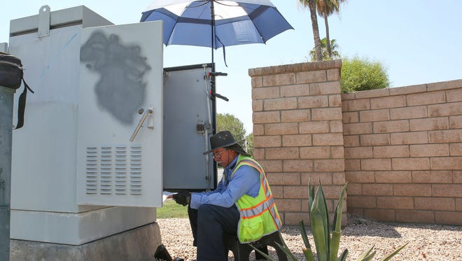 """Jesus Sanchez stays in the shade as he works on a traffic signal in Cathedral City during temperatures exceeding 117 degrees, June 20, 2017.   Sanchez said it was like """"working in a skillet,"""" of the temperatures."""