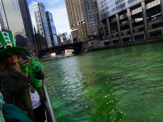 Spectators watch as the Chicago River is dyed green