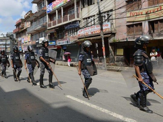 Nepalese police in riot gear walk past shuttered shops