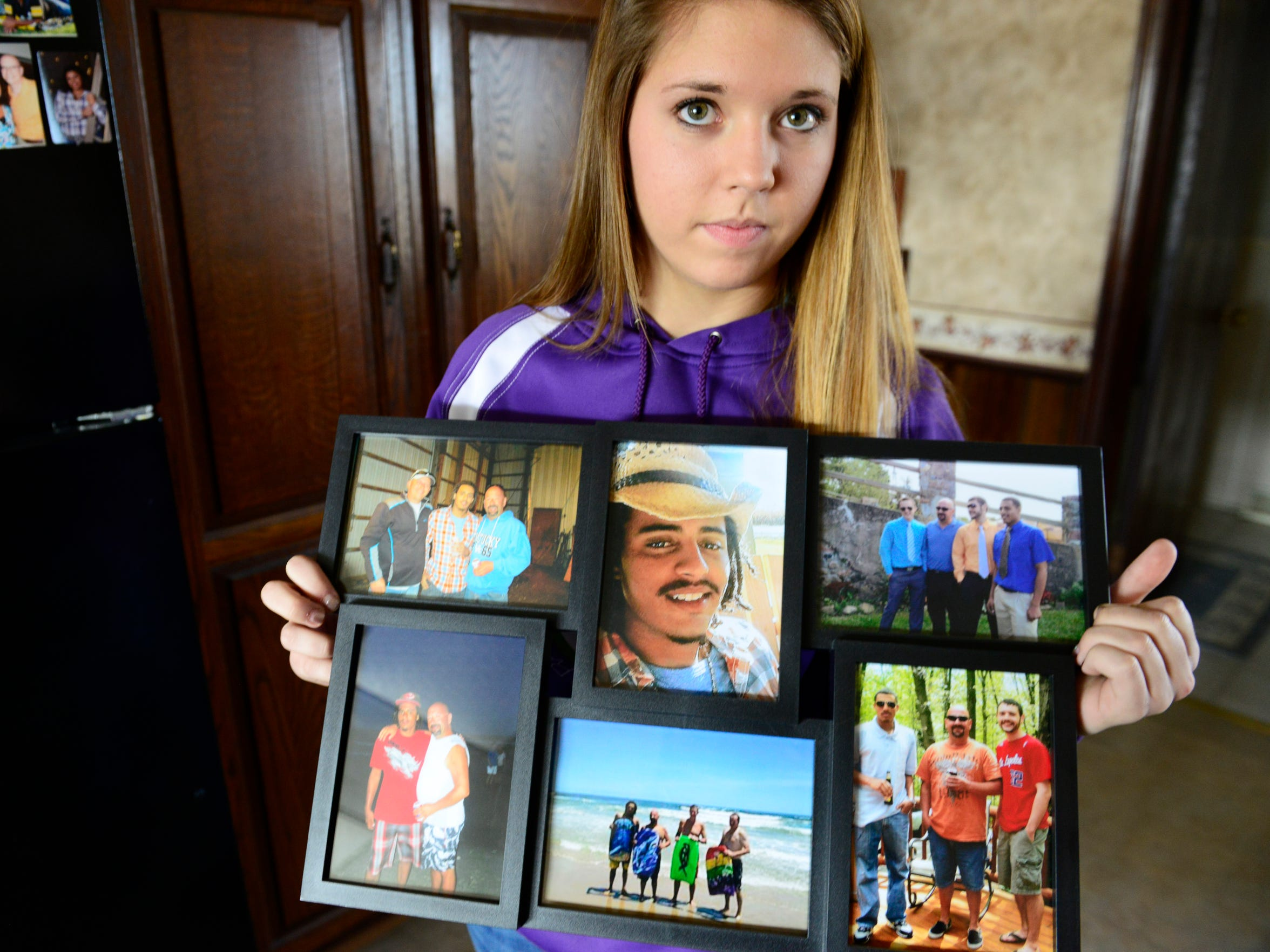 Bralyn Gregg holds family photos featuring her brother.
