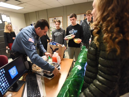 Sgt. Chris Carbone looks over the meals Kinnelon High's Future Business Leaders of America club brought over for police officers scheduled to work on Christmas Eve and Christmas Day.