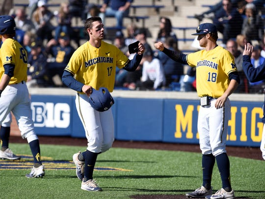 Michigan's Drew Lugbauer, left, and Jake Bivens bump fists.