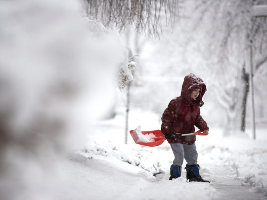 Lucas Sullivan, 6, shovels snow in front of his home as snow falls in Rutherford on Wednesday, March 7, 2018.
