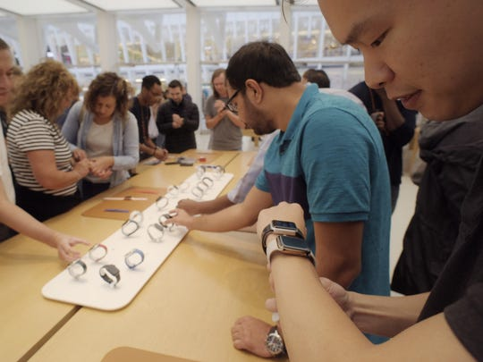 In this Sept. 21, 2018 file photo customers look at Apple Watches at an Apple store in New York.