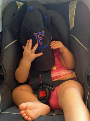 Isabella holds her father's Gators hat over her face in shame that he didn't wear a UF shirt on the team's opening day this past Saturday.