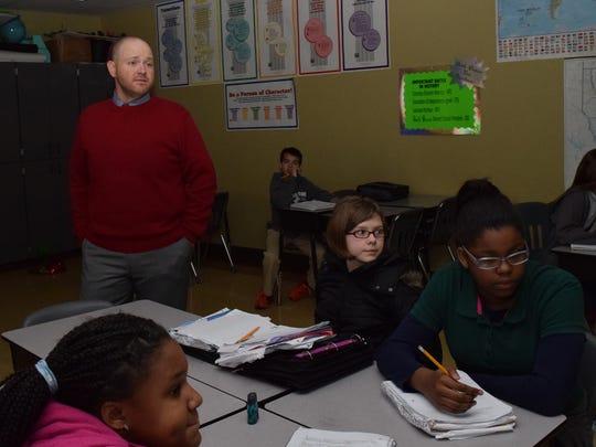 Joel Stevison (back, red sweater) is a middle school